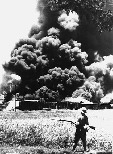 A Japanese soldier watching oil tanks near Jakarta set afire by the retreating Dutch, March 1942
