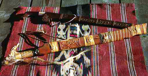 A ceremonial mandau (sword) and a work mandau (parang or otak) on doyo fiber veawing