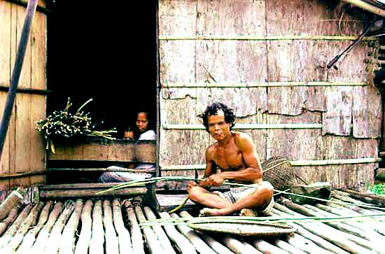 Karim and his wife, splitting rattan on his porch in the village Rantau Layung, Pasir