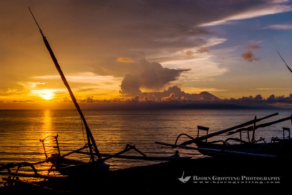 Indonesia, Nusa Tenggara, Lombok, Senggigi. The sun sets in the ocean, in the backgrund you can see Gunung Agung on Bali.