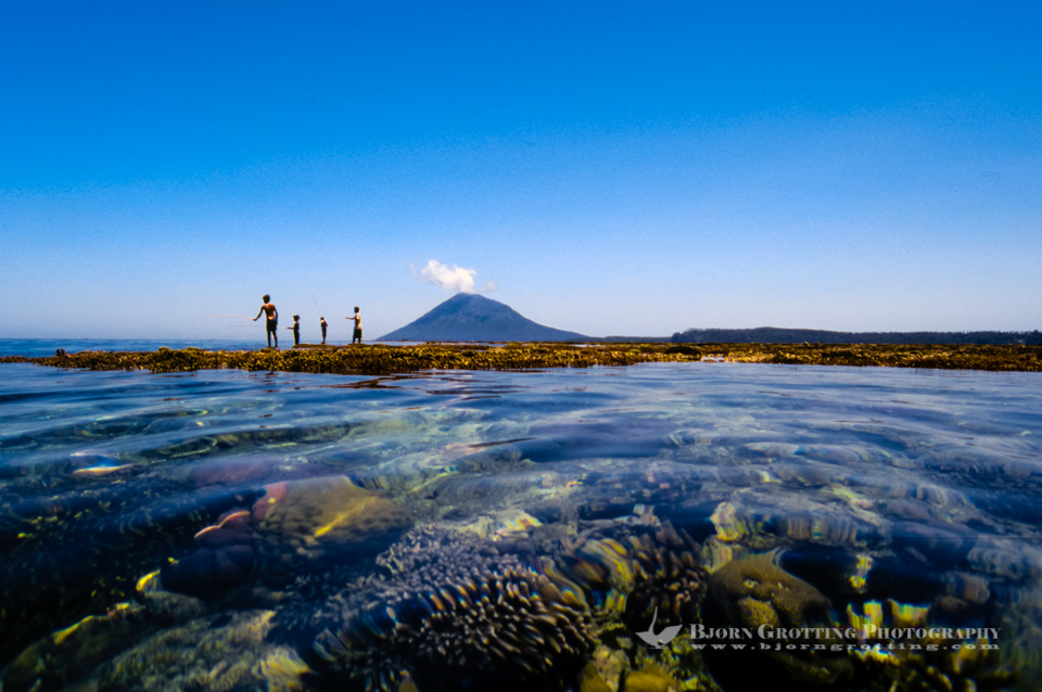 Indonesia, Sulawesi, Bunaken. Locals fishing on the reef with Manado Tua in the background.